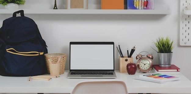 Local de trabalho confortável mínimo com laptop de tela em branco com mochila estacionária e escolar