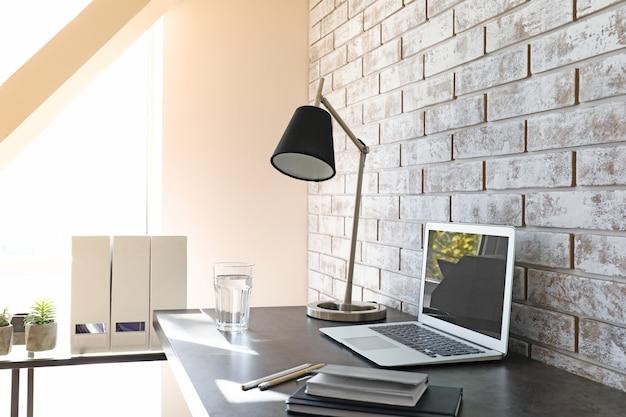 Local de trabalho confortável perto de uma parede de tijolos claros