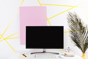 Local de trabalho criativo com monitor e folha de palmeira