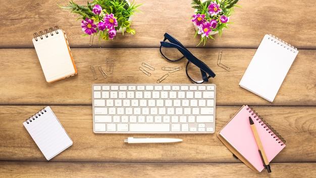 Local de trabalho criativo com teclado e cadernos