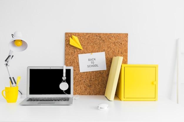 Local de trabalho criativo de aluno com placa de cortiça e laptop