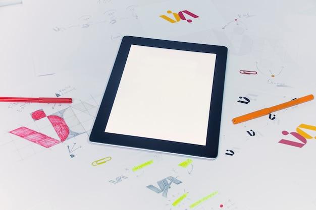 Local de trabalho criativo de um designer gráfico com tablet. desenvolvimento de logomarca para a empresa.