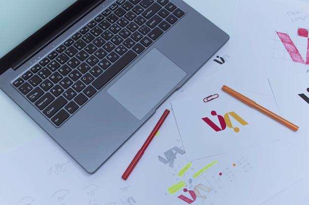 Local de trabalho criativo de um designer gráfico. desenvolvimento de logomarca para a empresa. desenhos e esboços em papel em um escritório de estúdio de arte.