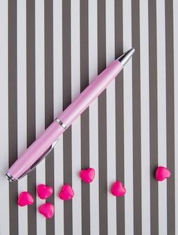 Local de trabalho criativo de uma designer de mulher, em uma mesa listrada de branco-preto, encontra-se uma caneta rosa e pequenas contas em forma de coração, vista superior de flatlay