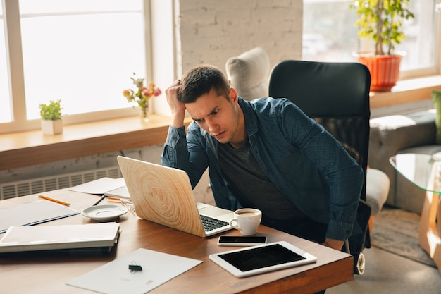 Local de trabalho criativo - espaço de trabalho organizado como você gosta para se inspirar. homem trabalhando no escritório em traje confortável, posição relaxada e mesa bagunçada. escolha a atmosfera desejada - ideal clara ou caótica.