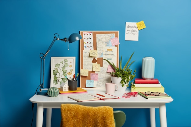 Local de trabalho criativo sem pessoas, bloco de notas aberto, abajur, quadro com notas para lembrar, planta interna em um vaso, caneca de bebida.