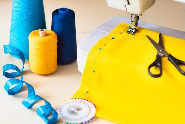 Local de trabalho da costureira. máquina de costura profissional no trabalho. a máquina de costura costura tecidos brilhantes, metros e fios coloridos para costura