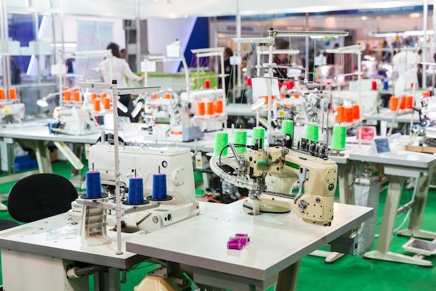 Local de trabalho da costureira, máquinas de costura na fábrica. máquina overloque, ninguém, costurar roupas em tecido. fabricação de tecidos