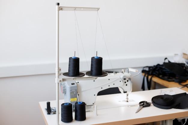 Local de trabalho da costureira na produção. máquina de costura em um fundo cinza