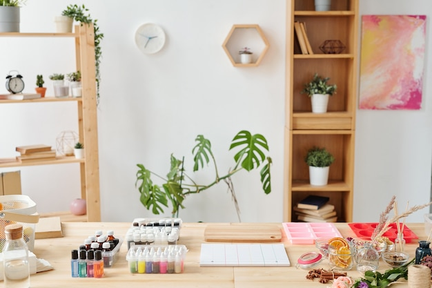Local de trabalho da saboneteira em estúdio com conjunto de óleos essenciais, perfumes, moldes de silicone para massa líquida e ingredientes naturais em mesa de madeira