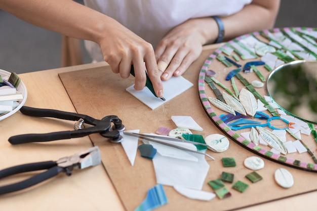 Local de trabalho das mãos das mulheres do mestre do mosaico segurando uma ferramenta para detalhes do mosaico no processo de fabricação ...