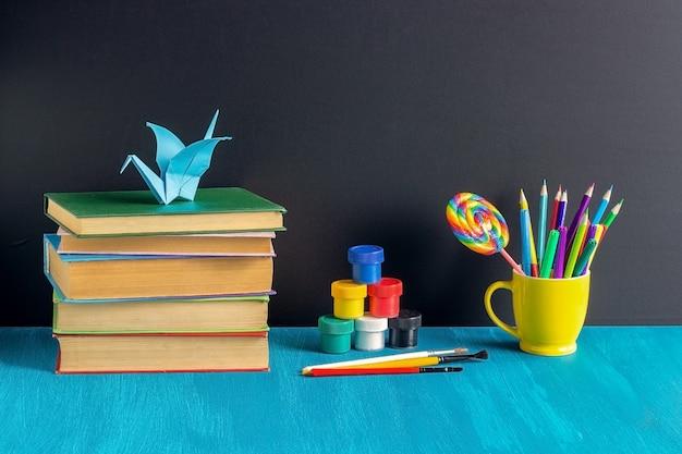 Local de trabalho de alunos. livros de papelaria tinta guache e origami guindaste na mesa azul