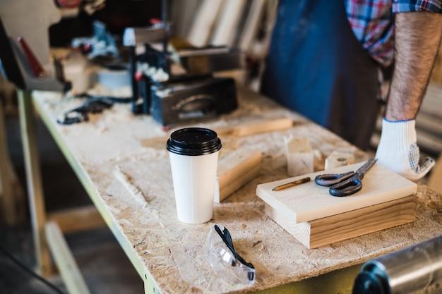 Local de trabalho de carpintaria moderna com tablet, café, tesoura e pedaços de madeira na mesa, na oficina