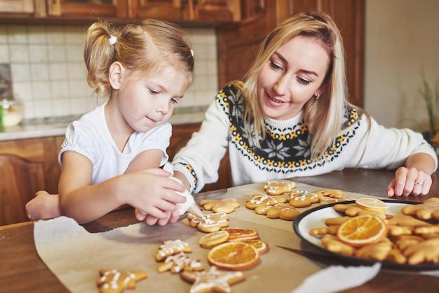 Local de trabalho de confeitaria com mãos femininas decorando biscoitos de natal. padaria em casa, doce ensolarado, férias de inverno.