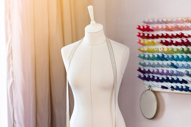 Local de trabalho de design com costurar manequins, bobinas com fios e fita métrica.