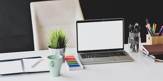 Local de trabalho de design com laptop de tela em branco aberto e material de escritório