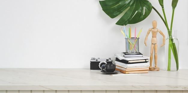 Local de trabalho de design minimalista com câmera e material de escritório na mesa branca