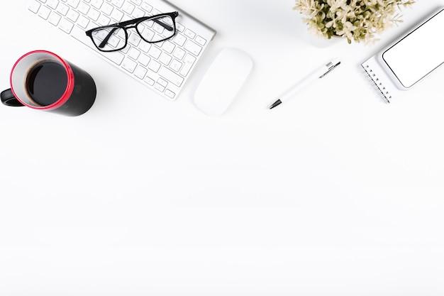 Local de trabalho de escritório acolhedor com teclado e copo