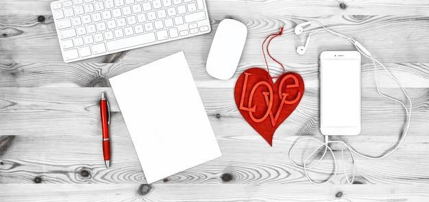 Local de trabalho de escritório com coração vermelho, teclado, telefone, fones de ouvido, papelaria e material de escritório. conceito de dia dos namorados com espaço para seu texto e imagens