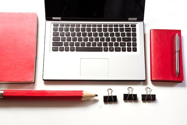 Local de trabalho de escritório com laptop, acessórios vermelhos