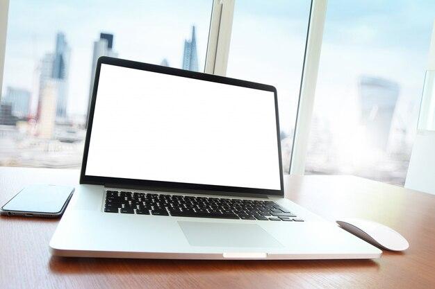 Local de trabalho de escritório com laptop de tela em branco e telefone inteligente na mesa de madeira