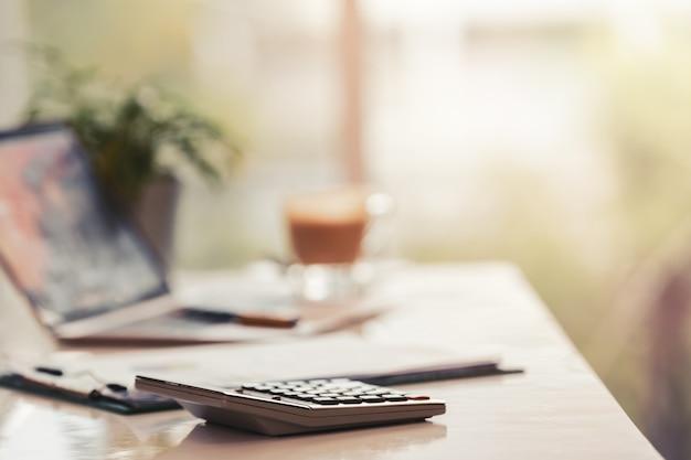 Local de trabalho de escritório com laptop e calculadora na natureza de mesa turva fundo