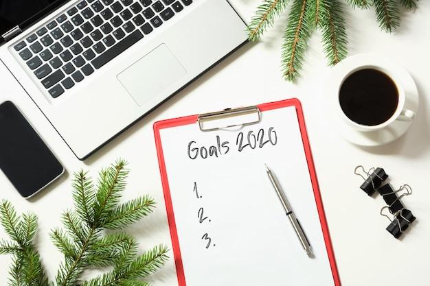 Local de trabalho de escritório com laptop e metas 2020 lista