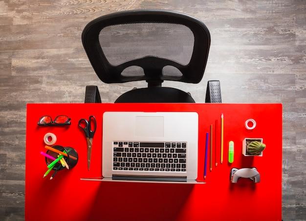 Local de trabalho de escritório com laptop e papelaria na mesa vermelha de madeira vermelha