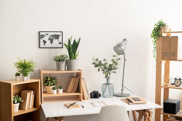 Local de trabalho de escritório com mesa com suprimentos, prateleiras de madeira com livros e vasos de flores e foto do mapa na parede