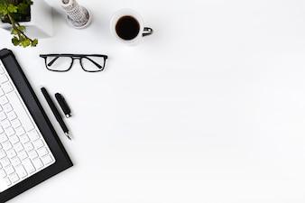 Local de trabalho de escritório com teclado e óculos