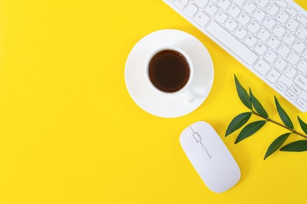 Local de trabalho de escritório com teclado, mouse de computador, xícara de café e planta em fundo amarelo. camada plana, vista superior
