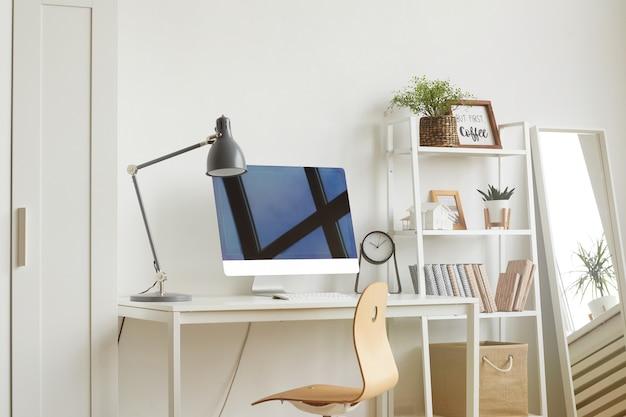 Local de trabalho de escritório em casa vazio com cadeira de madeira e computador moderno na mesa branca Foto Premium