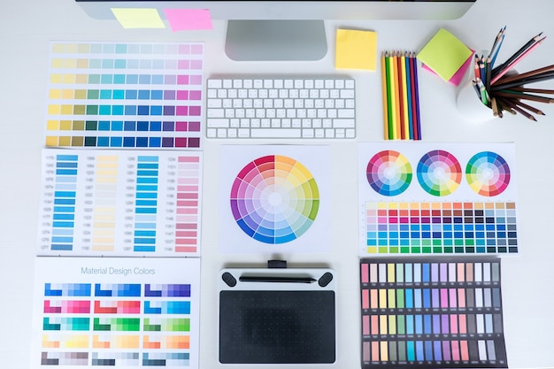Local de trabalho de escritório moderno com tablet, designer gráfico e amostras de amostra de cor no local de trabalho, área de trabalho de vista superior.