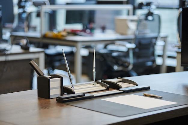 Local de trabalho de escritório moderno em grande corporação. mesa de trabalho confortável com artigos de papelaria, cadeira de couro para computador. chefe, chefe, supervisor ou chefe do local de trabalho da empresa.