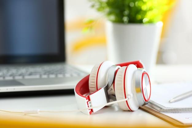 Local de trabalho de escritório remoto vazio com laptop e fone de ouvido