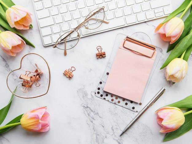 Local de trabalho de freelancer ou blogueiro com teclado, bloco de notas e tulipas