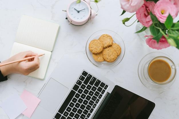 Local de trabalho de mulher bonita. laptop, biscoitos, flores. postura plana.