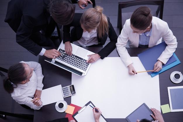 Local de trabalho de negócios com pessoas, xícara de café, tablet digital, smartphone, papéis e vários objetos de escritório na mesa