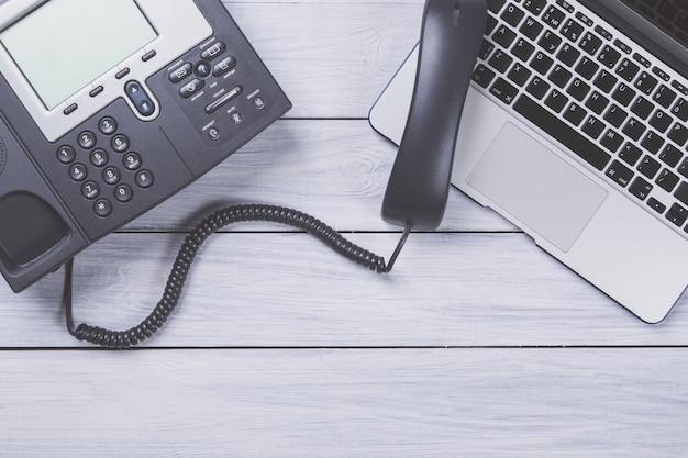 Local de trabalho de negócios com telefone moderno e laptop na mesa de madeira.