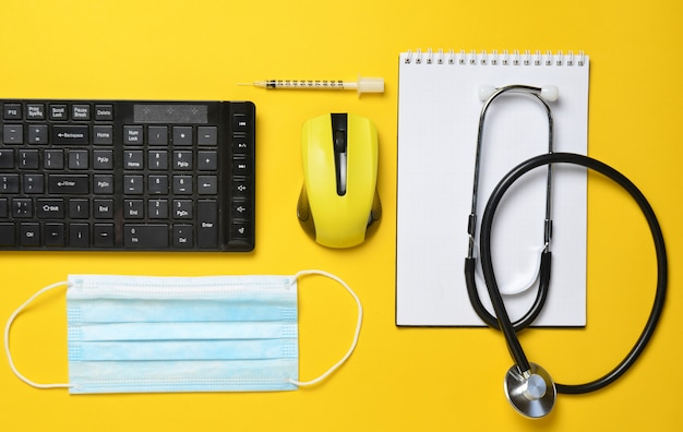 Local de trabalho de um médico moderno. teclado, mouse sem fio, caderno, estetoscópio, seringa em fundo amarelo, vista superior, tendência minimalista