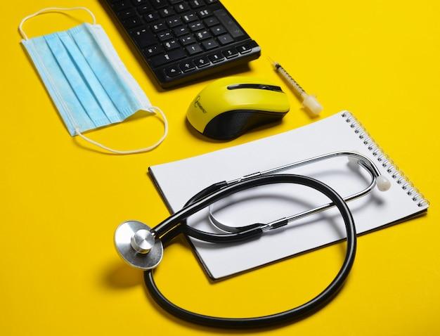 Local de trabalho de um médico moderno. teclado, mouse sem fio, caderno, estetoscópio, seringa em fundo amarelo.