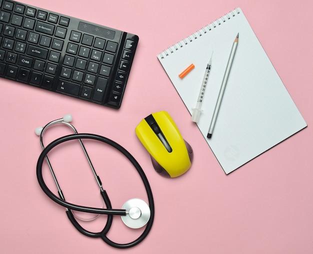 Local de trabalho de um médico moderno. teclado, mouse sem fio, caderno, estetoscópio, seringa em um fundo rosa pastel, vista superior, tendência minimalista
