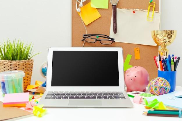 Local de trabalho de uma pessoa criativa com uma variedade de objetos coloridos de papelaria