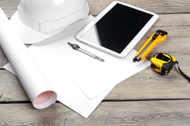 Local de trabalho do arquiteto com papel de planta e tablet digital com tela em branco