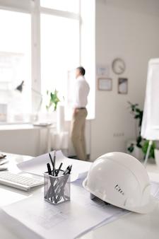 Local de trabalho do arquiteto moderno com capacete branco, monte de lápis e papéis com esboços no escritório