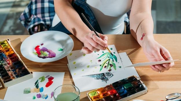 Local de trabalho do artista com rascunhos e materiais de paleta ao redor. pintor fazendo pinceladas de esboço, obtendo inspiração.