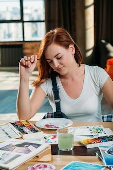 Local de trabalho do artista. inspiração. a pintora ruiva pensa olhando para as pinceladas com esboços e materiais de paleta ao redor.