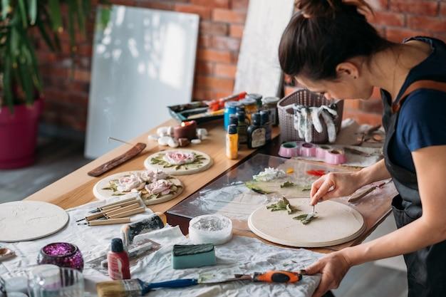 Local de trabalho do artista. inspiração. arte de flor em cerâmica em andamento. mulher com ferramentas de modelagem, trabalhando em estúdio.