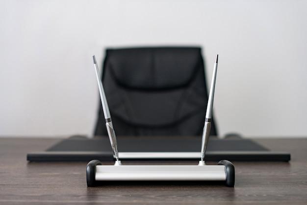 Local de trabalho do chefe de empresa: cadeira de couro, instrumentos de escrita.