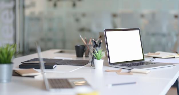 Local de trabalho do designer com laptop de tela aberta em branco